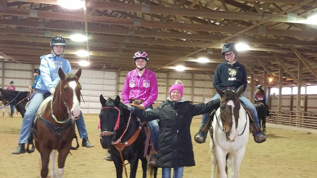 Andrea on Scout, Emma on Bandit, and Grace on Maverick with Coach Tracy.