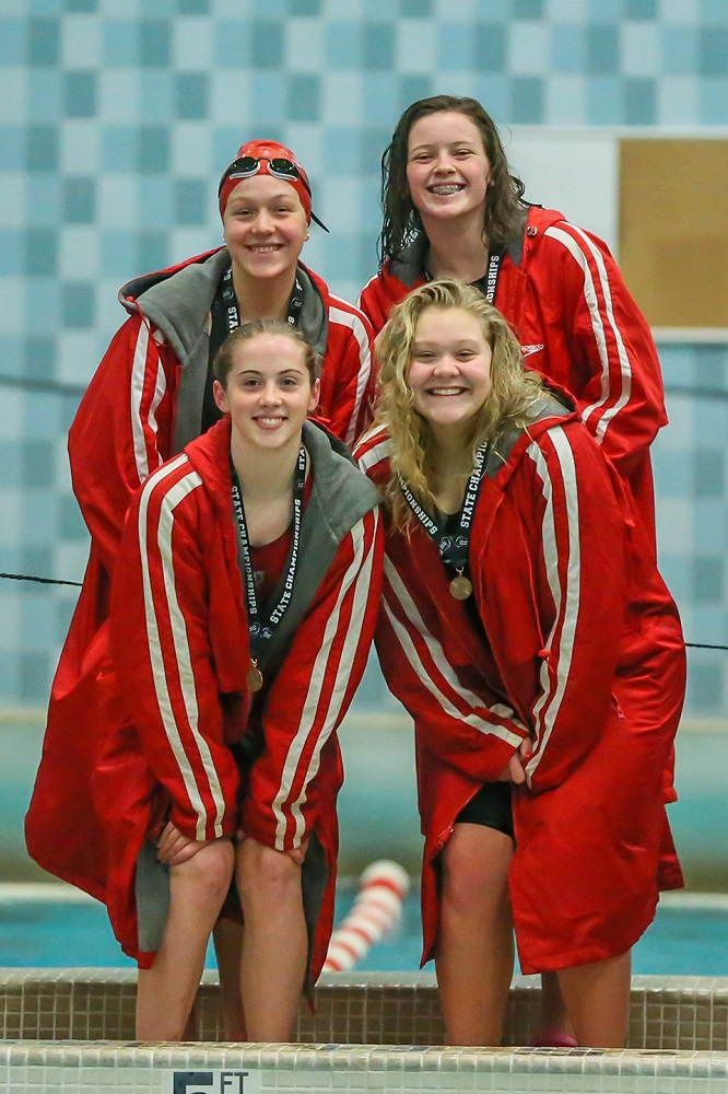 The WHS 200 Yard Medley Relay team pose on the podium after receiving their 6th place medals. They are: back row Ella Houwers and Brianna Zimdars and front row Morgan Radaj and Sophia Fanshaw. (Photo by Bob Mischka.)