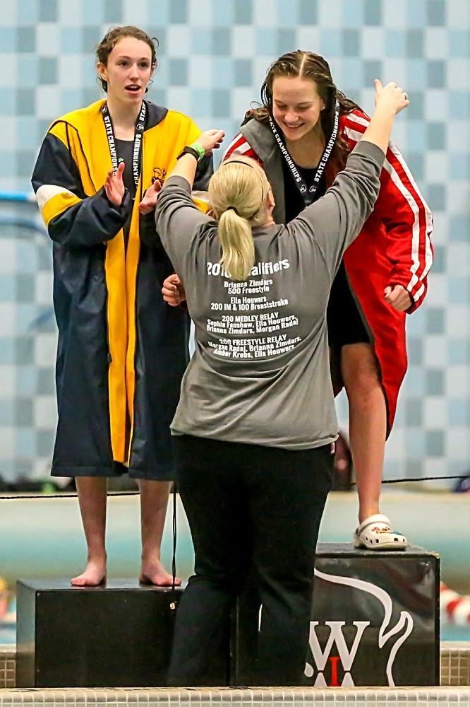 WHS Swimming Coach Gina Foucault has placed the 100 Yard Breaststroke Championship Medal around Ella Houwers' neck as she stood on the top of the podium. (Photo by Bob Mischka.)