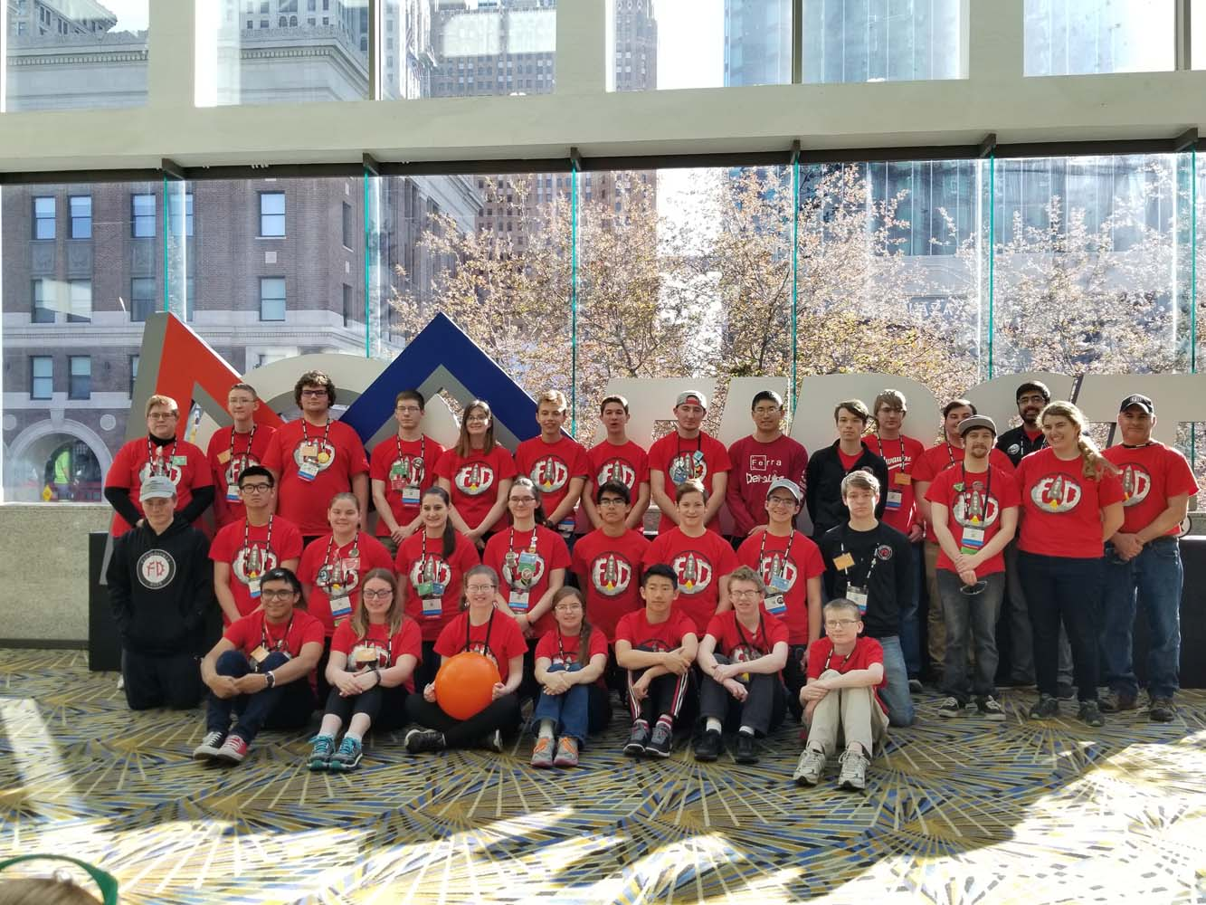 Team members and mentors pose for a photo in the lobby of the Cobo Center
