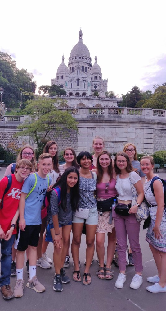 Posing in front of the Sacre Coeur basilica in Montmarte, the art district of Paris
