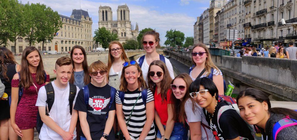 Students and Ms. Pasdera pose with Notre Dame in the background during a walking tour of Paris