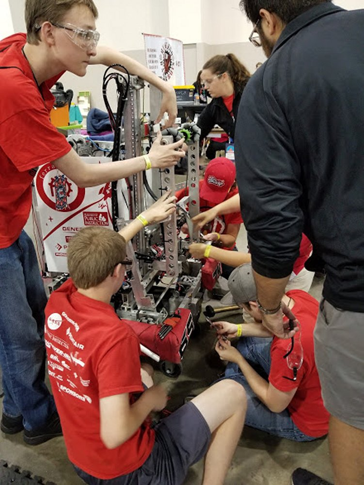 Team member scramble to duct tape the arm of the robot in the upright position before finals begin