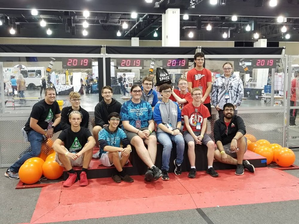 The drive teams from the winning alliance pose for a photo after the competition