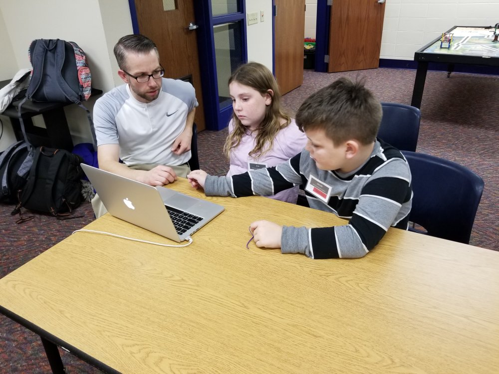 Mr. Nate Works with Students on their Project Presentation